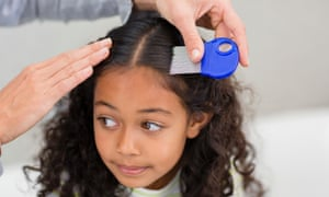 A mother goes through her daughter's hair with a nit comb.