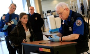 A TSA officer checks the identification of a passenger at an airport security checkpoint