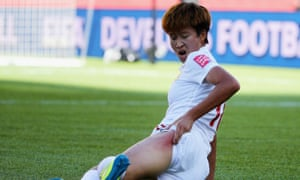 Lou Jiahui of China reacts after sliding on the artificial turf.