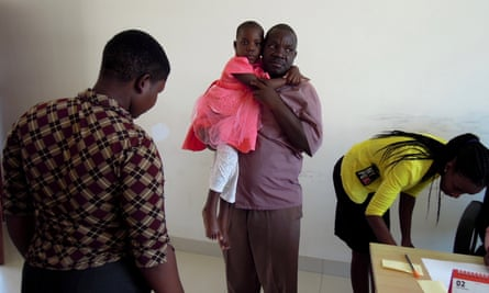 Dodo Boniface carries his daughter, Dainess, during a weigh-in at Bugando Medical Centre in Mwanza. Doctors are trying to assess whether Dainess is strong enough for a course of chemotherapy.
