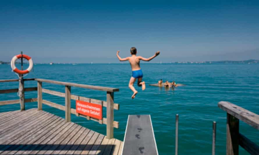 Boy jumping from a diving board into the Lake Constance, Bregenz, Austria