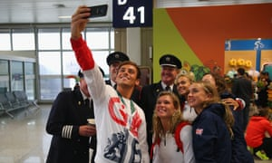 Tom Daley, Tonia Couch and Lois Toulson of Great Britain take a selfie with British Airways Captain Steve Hawkins and his crew as Team GB prepare to fly back from Rio.