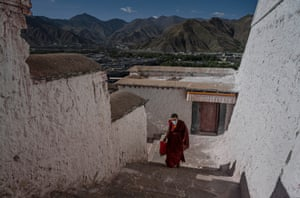 A Tibetan Buddhist monk walks up the stairs in the Potala Palace