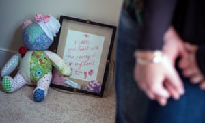 A shadow box of memories of their daughter, including her hand and foot prints, sits with a teddy bear.