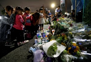 People pray for the victims of a stabbing in Kawasaki, Japan