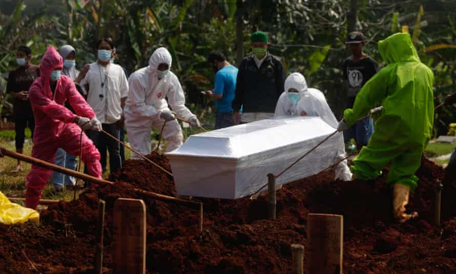 Workers bury a man with code-19 who died during a last rites at a cemetery in Dipok, Indonesia