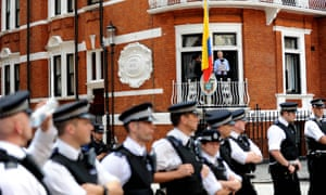 Assange gives a statement from the balcony of the embassy while police officers stand guard in August 2012