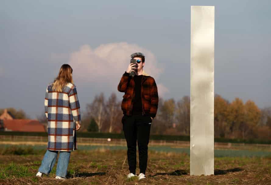 People inspect a metal monolith in a field in Baasrode, Belgium, this week.