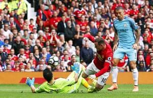 Manchester City goalkeeper Claudio Bravo clatters into Wayne Rooney ...