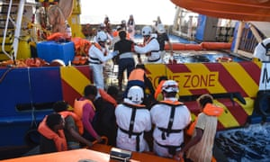 People are helped aboard the Topaz Responder ship during a rescue operation in the Mediterranean Sea