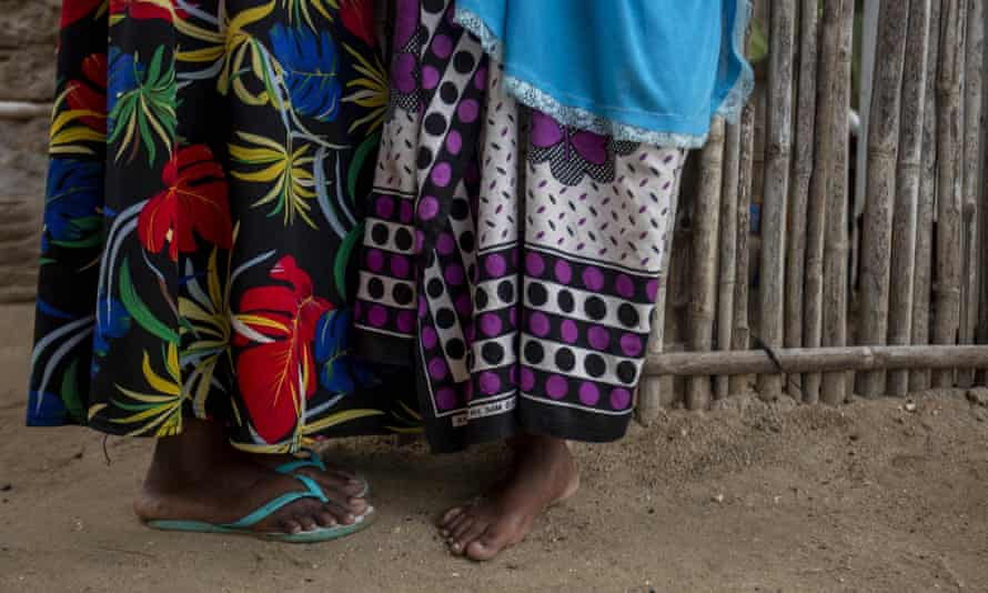 Two women, seen from the waist down in colourful dresses, stand in Paquitequete, a neighbourhood of Pemba City