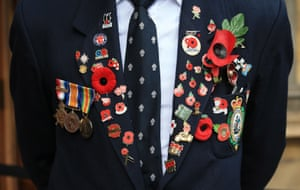 A veteran wears a collection of medals and commemorative poppies on the breast of his jacket at the Westminster Abbey Field of Remembrance, London