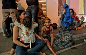 People wait to receive treatment outside a hospital following the explosion in the Lebanese capital.