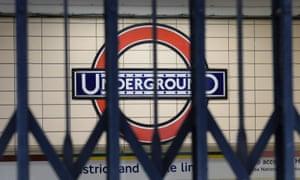 A London Underground sign seen through closed gates