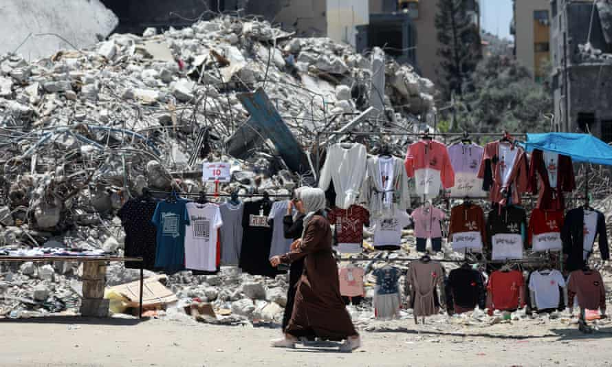 A Palestinian street vendor sells clothes near the rubble of al-Shuruq tower in Gaza city.