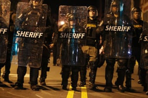 Law enforcement officials in riot gear force people off a street as they protest the killing of Andrew Brown Jr.