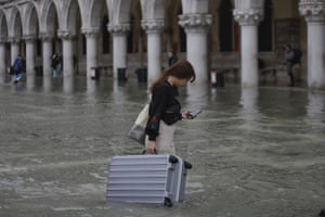 A tourist carries her luggage in a Piazza San Marco