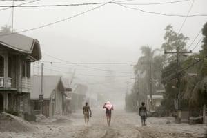 Residents evacuate the ash-choked streets of Batangas