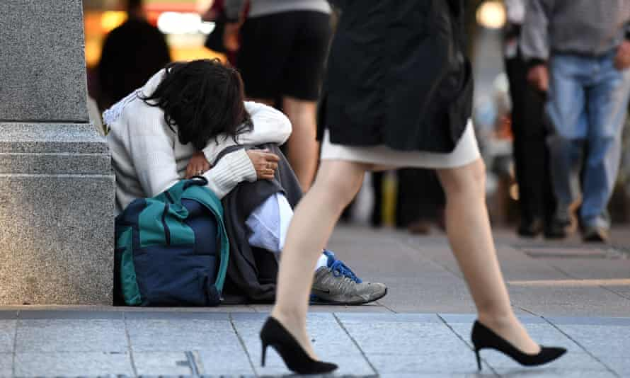 A homeless woman sits on a street corner in central Brisbane