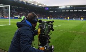 A camera operator at a live football match