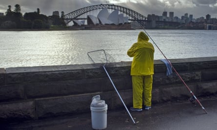 fisherman in yellow oilskins looks out onto opera house and harbour bridge