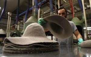 A man piles felt hats inside Borsalino's hat factory, in Spinetta Marengo