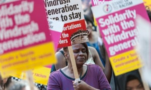 A demonstrator with a sign reading 'Windrush generation: here to stay'
