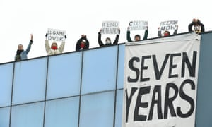 people with placards and large banner on a roof