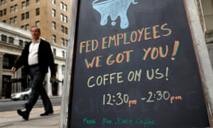A worker passes a cafe offering free coffee to federal employees near the the White House during the government shutdown in Washington in January 2018.
