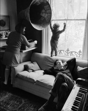 A young William Miller peers out the window under the watchful eye of his mother Rachel as his father Jonathan dozes on the sofa.