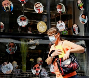 A woman passes by a shop window with masks on display in Vienna, Austria.