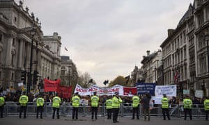 Protestors demonstrating against Modi hold placards by Parliament Square