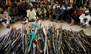 Members of the Yansakai vigilante group sit inside an auditorium in Gusau after surrendering more than 500 guns to the Zamfara state governor in December.