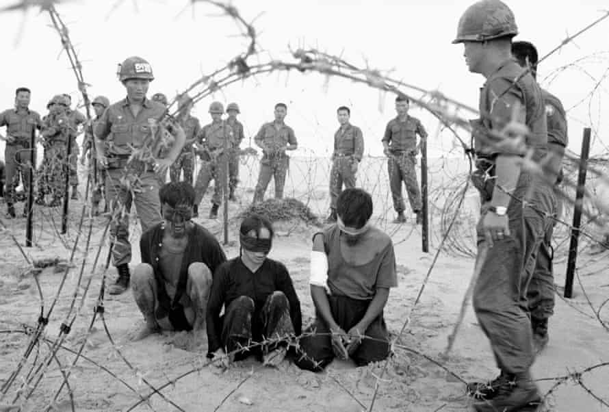 Korean troops guard three Vietnamese captives found near a village south of Tuy Hoa in November 1966