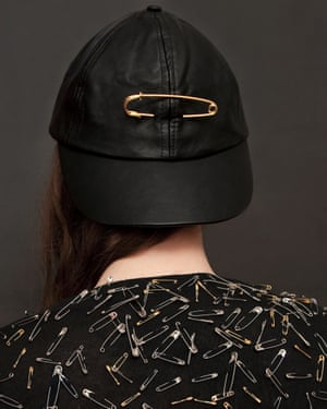 A woman wearing a baseball cap with a gold safety pin, from photographer Olivia Locher's I Fought the Law series