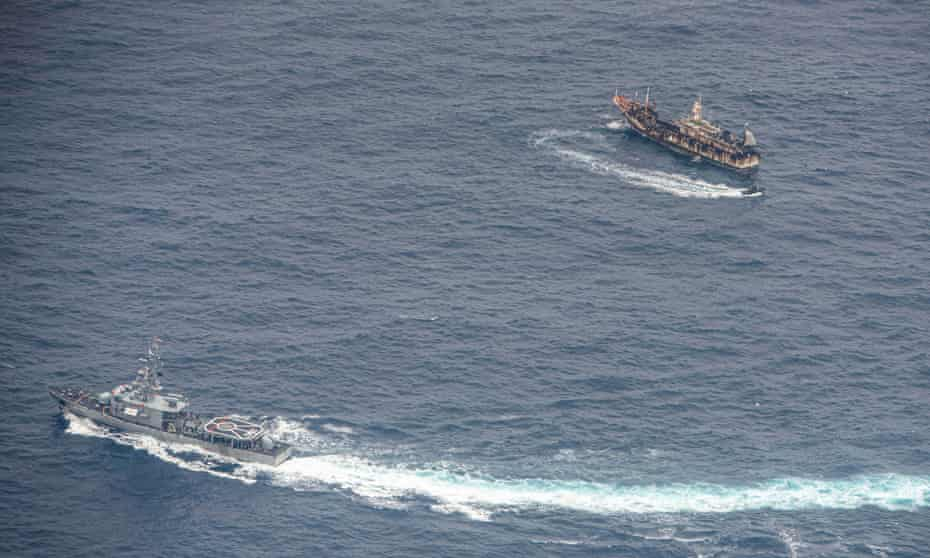 An Ecuadorian navy vessels challenges a fishing boat on 7 August after a fleet of mostly Chinese-flagged ships were detected in the Pacific Ocean.