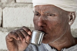 A man drinking from a small metal cup