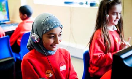 Muslim girl in headscarf  in primary school classroom in the UK