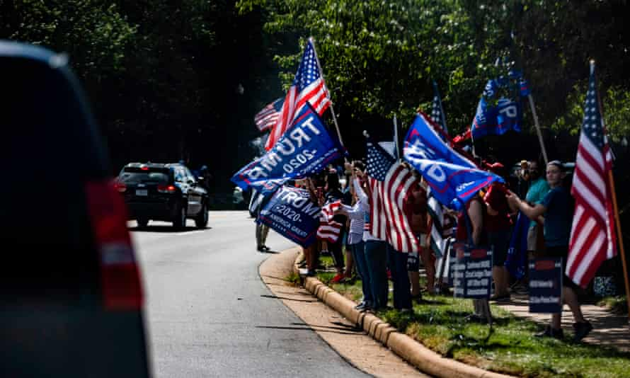 Supporters of Donald Trump stand with signs and flags as his motorcade leaves his golf club on Sunday in Sterling, Virginia..