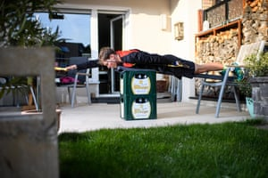 Triathlete Lasse Lührs performs dry swimming training on beer crates at his girlfriend's house in Wesselingen.