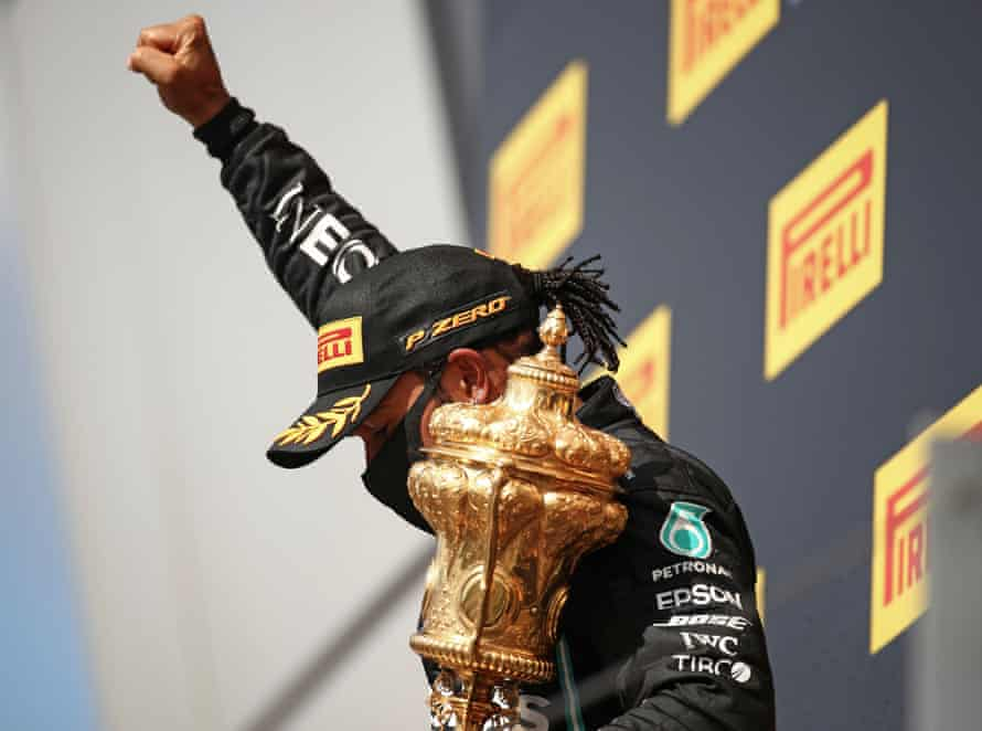Hamilton celebrates on the podium with a black power salute after winning the British Grand Prix at Silverstone on 2 August.
