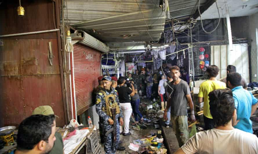 People and security forces gather at the site of a bombing in Al-Wahaylat market in Sadr City, Iraq, Monday, July 19, 2021. A roadside bomb attack targeted a Baghdad suburb on Monday, killing at least 18 people and wounding dozens in a crowded place.  Iraqi security officials said.  (Associated Press/Khaled Muhammad)