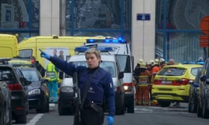 A police woman gestures in front of ambulances at the scene of a blast outside a metro station in Brussels