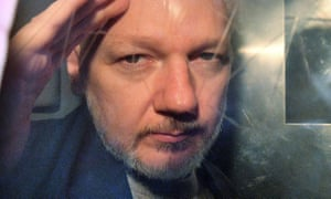 Julian Assange gestures from the window of a prison van as he is driven out of a London court in May 2019