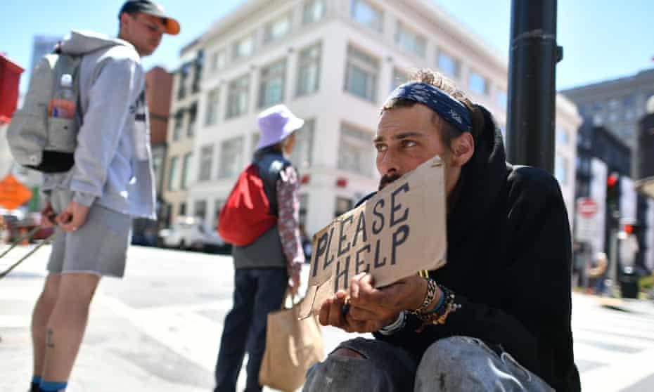 Homeless man begs along a sidewalk in downtown San Francisco