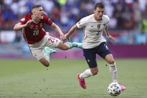 Hungary's Roland Sallai is airborne as he challenges for the ball with France's Benjamin Pavard.