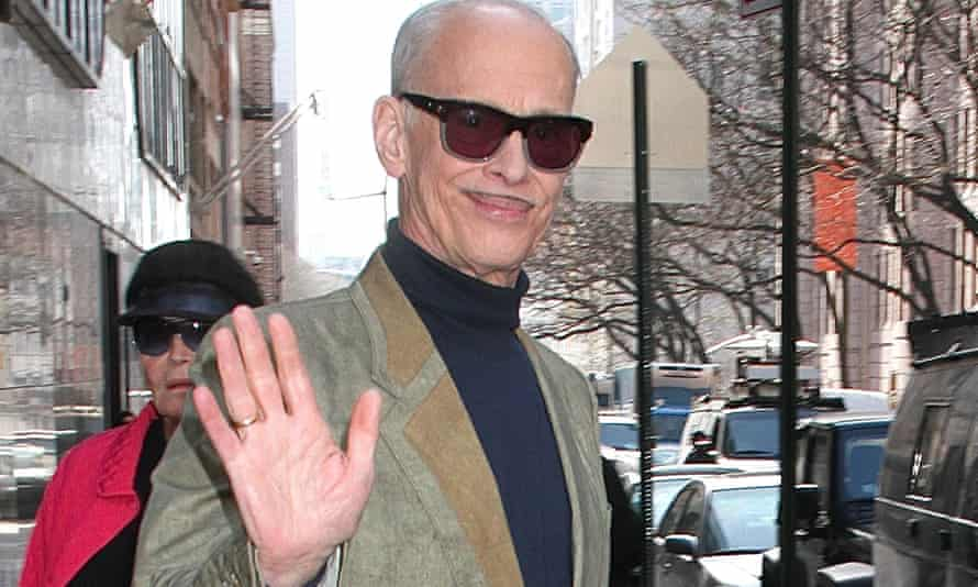 John Waters in dark glasses on a street, holding up a hand