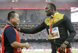 <strong>Beijing, China </strong>Men's 200m gold medalist Jamaica's Usain Bolt, receives a gift from a television cameraman who knocked him over with his Segway following his win in the 200m final at the World Athletics Championships at the Bird's Nest stadium