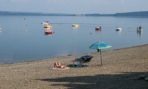 People sunbathing on a deserted beach by Lake Bracciano, Italy