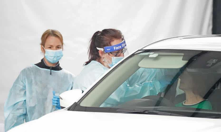 A medical worker takes a sample from a person at a drive-through Covid-19 pop-up testing clinic in Melbourne.